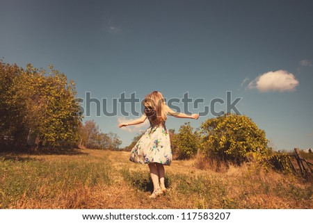 blond young woman in silky dress run in sunny meadow - stock photo
