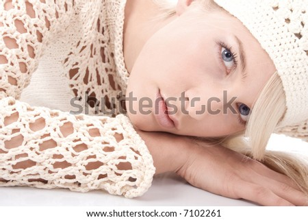 blond young woman in sweater lying on the floor, studio shot - stock photo