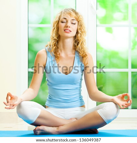 Blond young woman meditating, indoors - stock photo