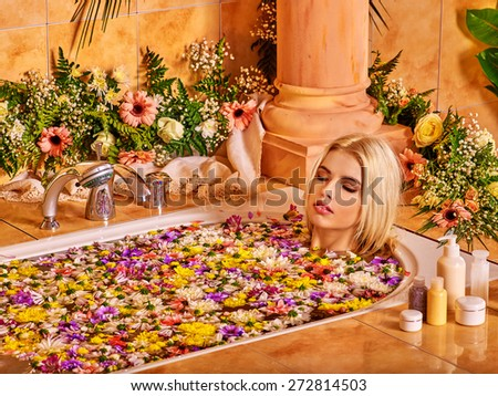 Blond young woman relaxing at water spa. - stock photo