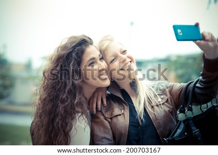 blonde and brunette beautiful stylish young women selfie in the city - stock photo