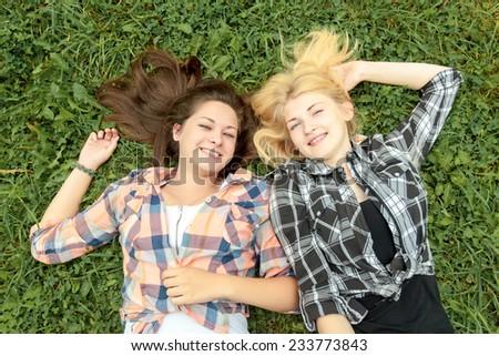 Blonde and brunette girl having break on a grass - stock photo