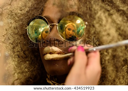Blonde artist painting gold lips with tassel reflected in the sunglasses of fashion African or Black American model wearing bright makeup and accessories - stock photo