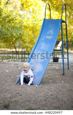 Blonde baby boy on a childrens slide at the playground, summer outdoors - stock photo