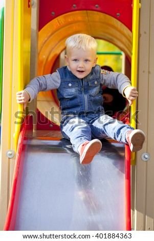 Blonde baby boy sits on a childrens slide at the playground, summer outdoors - stock photo