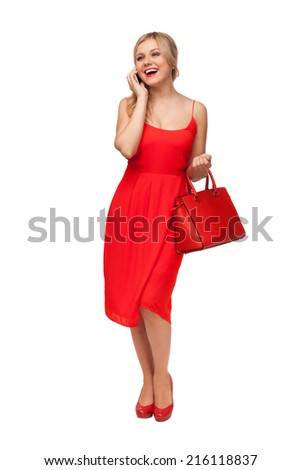 blonde beautiful woman in red dress holding big bag  talking on the cell phone isolated on white - stock photo