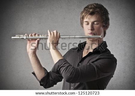 Blonde boy playing a clarinet - stock photo