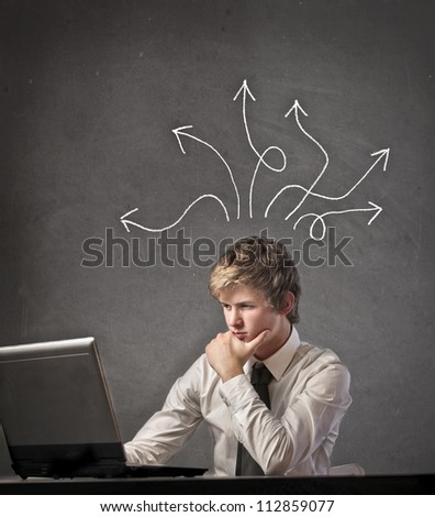 Blonde boy using the computer is searching a resolution to a problem - stock photo