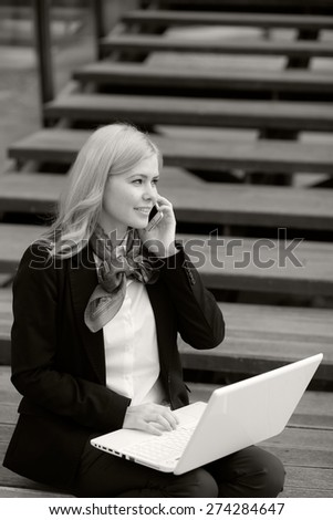 Blonde business woman with laptop and phone. Black and white photography - stock photo