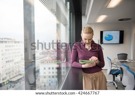 Blonde businesswoman in casual  clothes working on tablet computer at modern startup business office interior. Young people group on team meeting blured  in background - stock photo