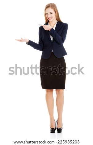 Blonde businesswoman inviting to an office - stock photo