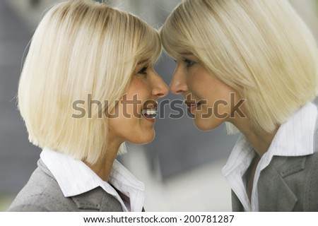 Blonde businesswoman smiling looking at mirror reflection - stock photo
