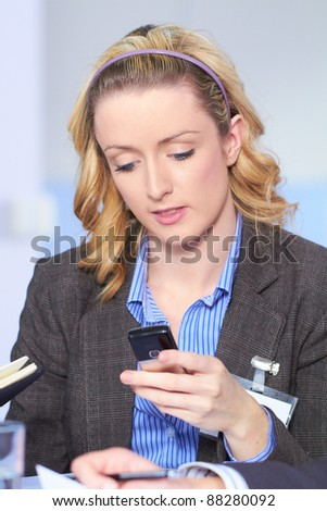 Blonde businesswoman using her mobile phone, blue shirt and business suit - stock photo
