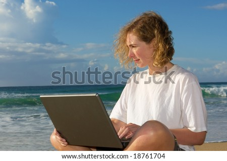 Blonde businesswoman with notebook on beach - sunrise light. Shot in Sodwana Bay Nature Reserve, KwaZulu-Natal province, Southern Mozambique area, South Africa. - stock photo