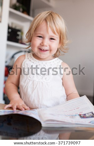 blonde caucasian baby two years old cute face looking at camera with happy smiling expression wearing a white dress or summer shirt thumbing and reading a magazine indoor home - stock photo