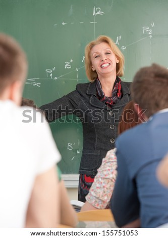 Blonde caucasian teacher giving a lecture to her students - stock photo