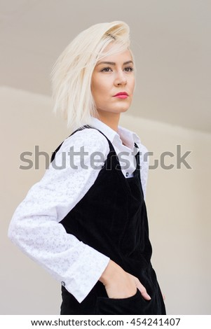 Blonde Caucasian woman posing in black and white outfit. - stock photo
