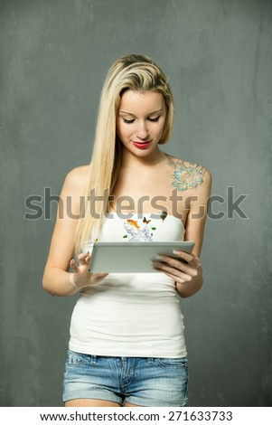 Blonde caucasian woman standing with tablet over grey background - stock photo