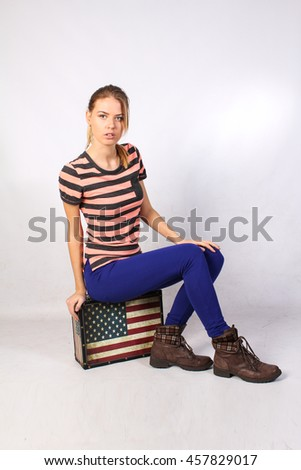 Blonde cheerful young woman is sitting on a suitcase like an American flag. Stars and stripes. Beauty portrait, perfect makeup. Isolated on white background - stock photo
