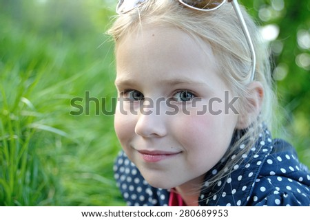 Blonde cute little girl smiling in a park close-up - stock photo