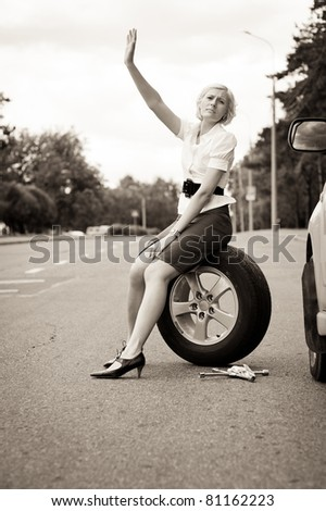 Blonde girl asks for help on the road near her broken car. Toned image - stock photo