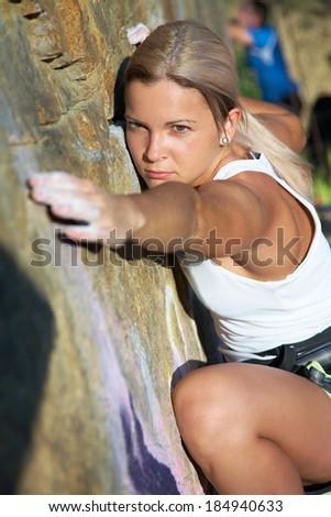 Blonde girl climbing on the rock. Close. - stock photo