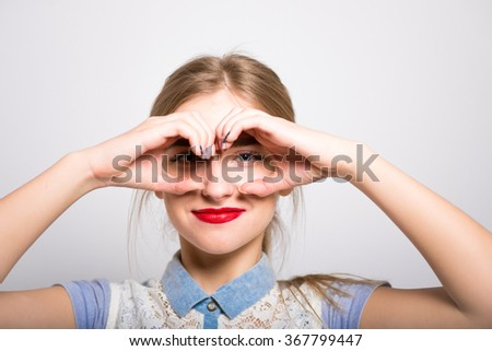 blonde girl doing hands binoculars isolated - stock photo