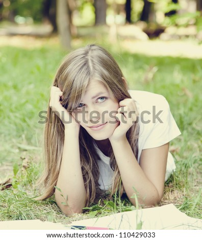 Blonde girl doing homework at the park. - stock photo