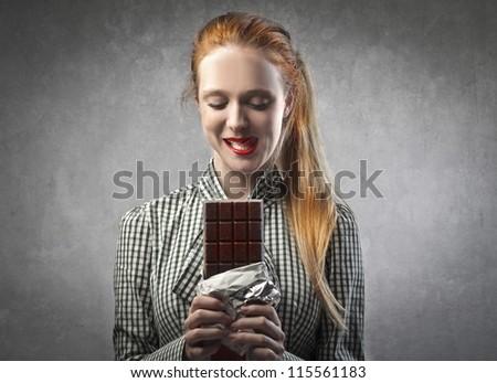Blonde girl eating a chocolate bar - stock photo