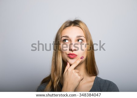 blonde girl has a good idea to clean skin, lifestyle concept studio photo isolated on a gray background - stock photo