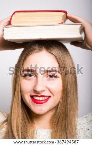 blonde girl holding a book on her head isolated - stock photo