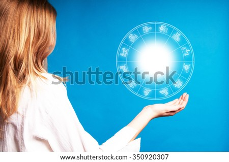 blonde girl holding an astrology chart in the air - stock photo