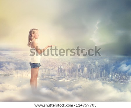 Blonde Girl  Holding Hand Out with Palm Up on the Clouds Above the City - stock photo