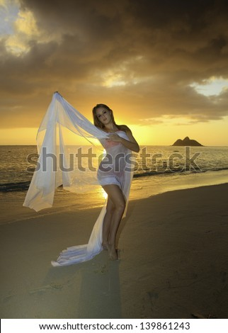 blonde girl in bikini at sunrise on the beach - stock photo