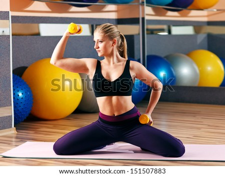 blonde girl in the gym performs exercises - stock photo