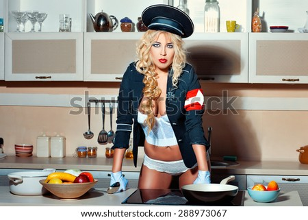 Blonde girl in the kitchen. She is wearing uniform cap and jacket. She lace underwear. Humorous awards in the form of a cross. - stock photo
