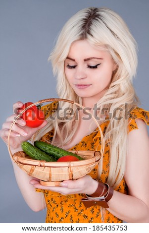 blonde girl lays down a basket of tomatoes and looking down - stock photo