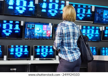 Blonde girl looks at LCD TVs in supermarket - stock photo