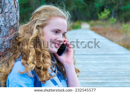 Blonde girl phoning mobile in nature - stock photo