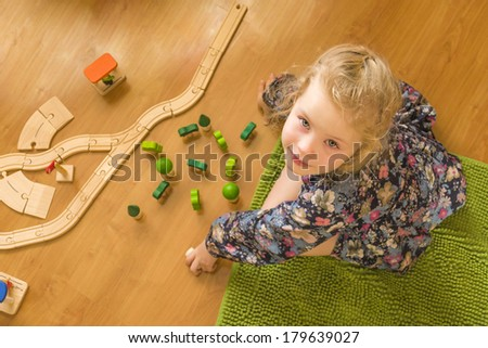 Blonde girl playing on the floor with a wooden rail and gazing into the lens below - stock photo