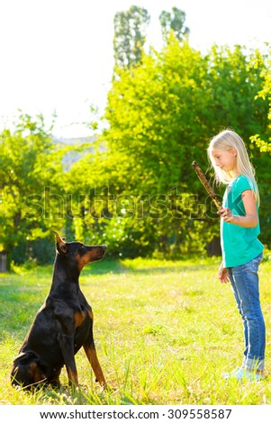 blonde girl playing with the dog or doberman in summer park - stock photo