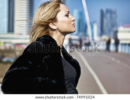Blonde girl pose near railing of bridge - stock photo