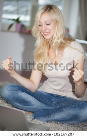 Blonde girl rejoicing while is using a laptop computer - stock photo