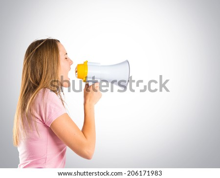 Blonde girl shouting with a megaphone over grey background  - stock photo