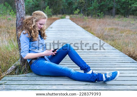 Blonde girl sitting on wooden path  phoning mobile in nature - stock photo