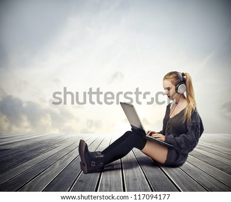 Blonde girl using a laptop computer outdoor - stock photo