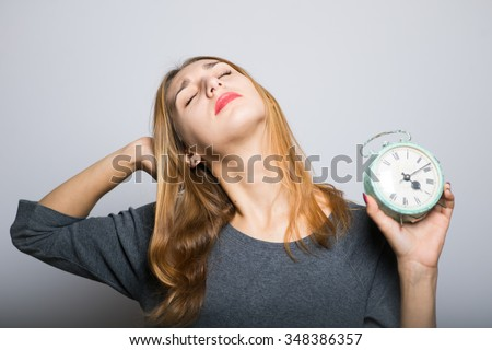 blonde girl wakes up with an alarm clock in hands, studio photo isolated on a gray background - stock photo