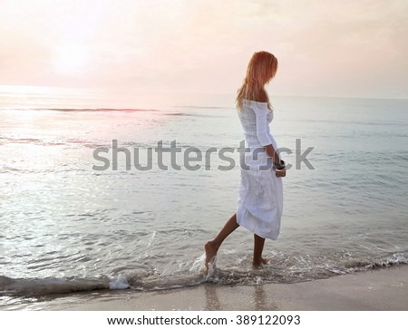 blonde girl walking by the sea in the sunset - stock photo