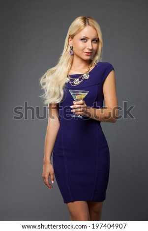 blonde girl wearing evening dress drinking martini over grey background - stock photo