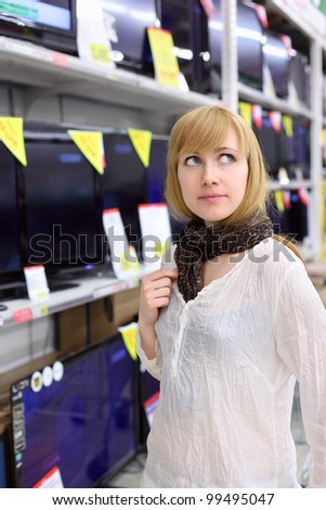 Blonde girl wearing scarf thinks about buying TV in supermarket; shallow depth of field - stock photo